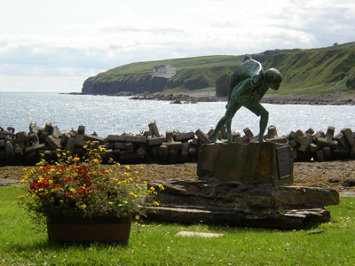 The statue of the World Famous Writer Neil M Gunn's character 'Kenn with Salmon' from the novel 'The Highland River' with the castle in the background.